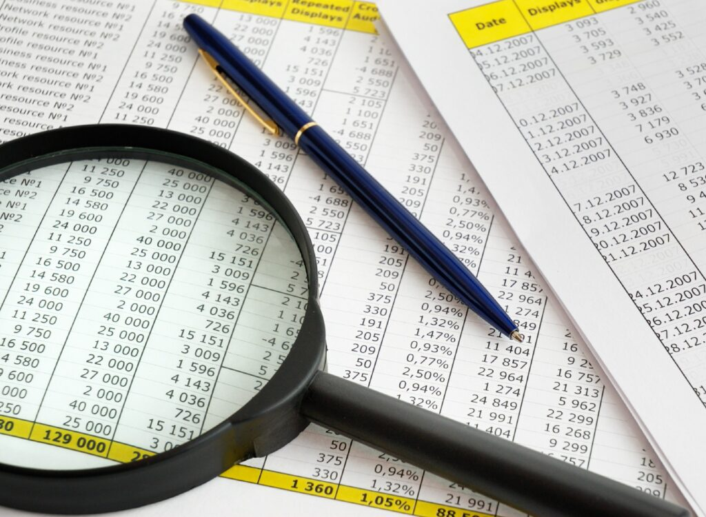 magnifying glass and pen on financial print outs